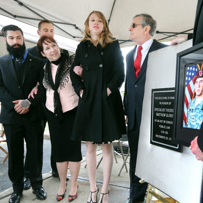 The Glende family gathers around a plaque during a