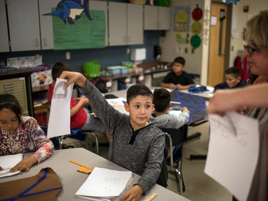 In this March 31, 2017, file photo, a fifth grade student shows his geometry work to a teacher at Columbus Elementary School in Columbus, New Mexico.