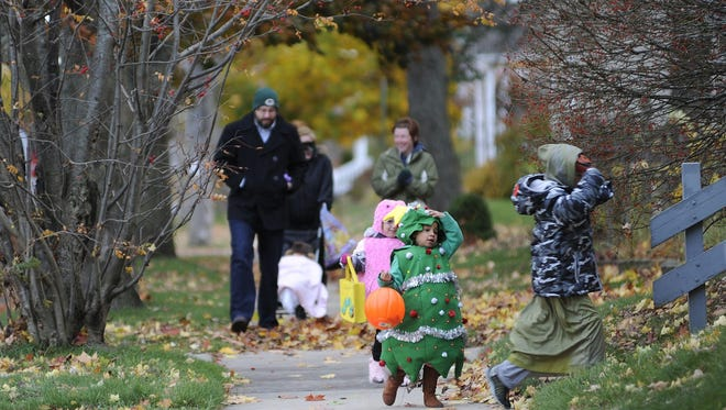 Caleb Worley, right, Reyana Jansen and Samantha Munden go trick-or-treating on Halloween in Manitowoc in 2014.