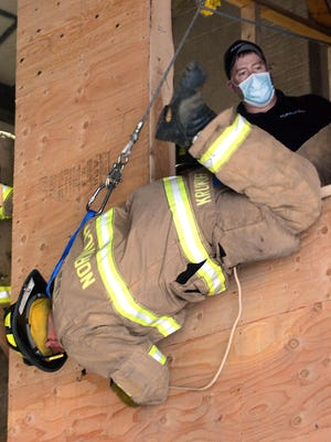 Norwich firefighter Will Krukoff uses the department's new Personal Escape System to bailout of a window Thursday under the instruction of Greenwich Fire Department Lt. Ryan Brainerd, right, at the Emergency Operations building in downtown Norwich. See videos and more photos at NorwichBulletin.com