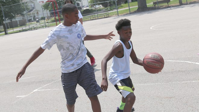 Feree Kent, 13, dribbles the ball around Jacob Day-Anderson, 14, on the courts at Johns Park in Mansfield. Both belong to a community basketball league that will support local children and their families.