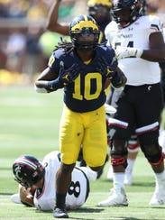 Michigan's Devin Bush celebrates a sack on Cincinnati's