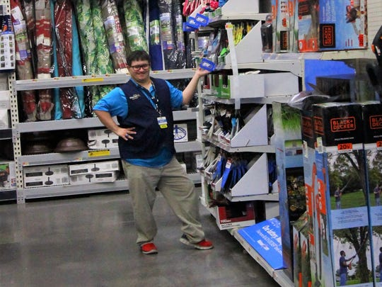 Isaiah Romero places an item on the shelf at the Ruidoso Downs garden center store.