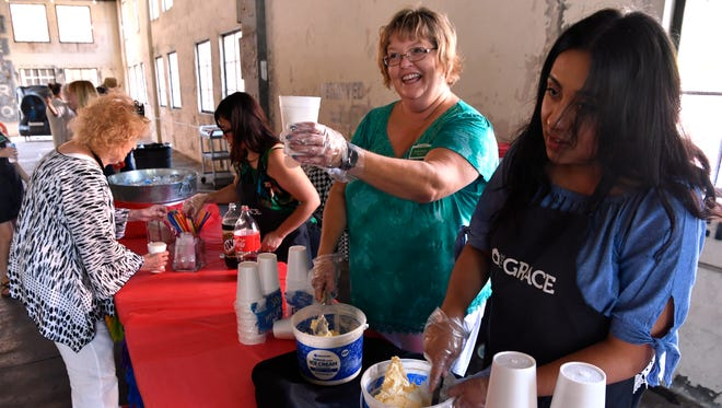 Sheila Scevers offers a cup of ice cream to a visitor as Yoleny Palacios scoops more Tuesday in The Grace Museum's spruced-up garage. The museum celebrated the new look by offering ice cream floats to all who came to visit.
