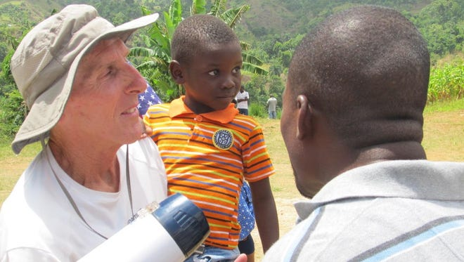 Tim Muth, left, holds a Haitian child during 2014 Vacation Bible School in Durrisy, Haiti.