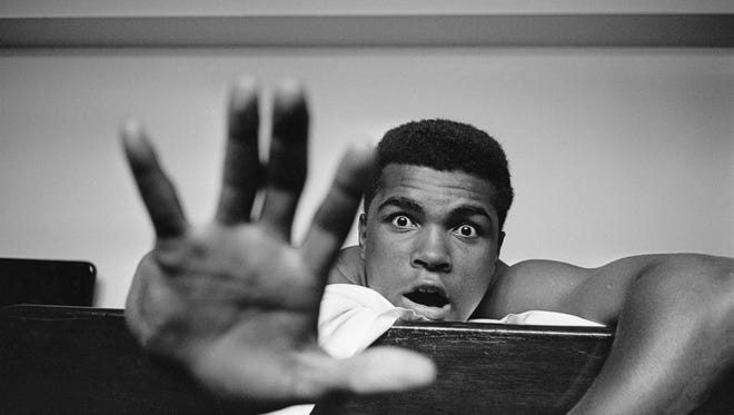 American Heavyweight boxer Cassius Clay (later Muhammad Ali) lying on his hotel bed in London. He holds up five fingers in a prediction of how many rounds it will take him to knock out British boxer Henry Cooper in 1963.