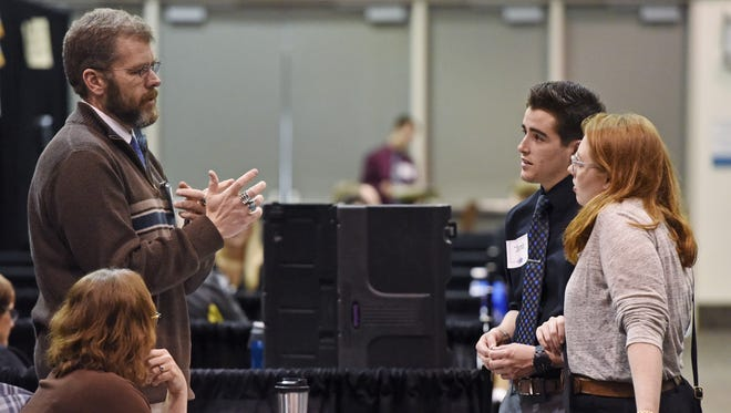 Chris Ostgaard of the Pinon Unified School District in Pinon, Arizona talks with Jacob Brower and Hannah Loefke Tuesday at a teacher job fair at the Sioux Falls Convention Center, March 15, 2016. Brower graduated last year and Loefke graduates this year, both from Northern State and are looking for their first full-time teaching jobs.