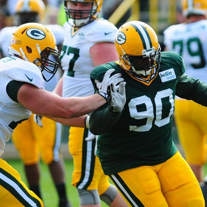 Green Bay Packers defensive tackle B.J. Raji, right, works against center/guard JC Tretter during training camp practice at Ray Nitschke Field, Monday, July 28, 2014.
