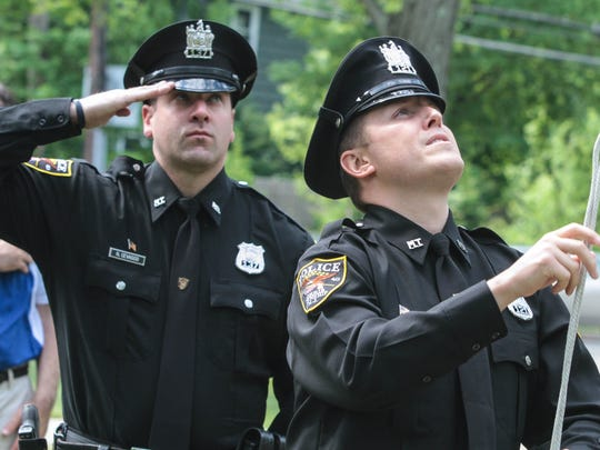 Officer James Perruso does the honorary raising of the flag as Officer Nick Cevasco looks on during the Memorial Day ceremony before the start of the parade in Morristown.