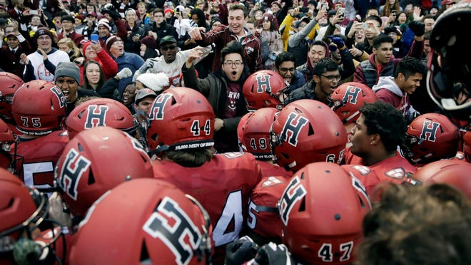 FILE - In this Nov. 17, 2018, file photo, Harvard players, students and fans celebrate their 45-27 win over Yale after an NCAA college football game at Fenway Park in Boston. Harvard defeated Yale. The Ivy League has canceled all fall sports because of the coronavirus pandemic.