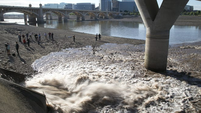Water begins to refill Tempe Town Lake, April 12, 2016, from a storm drain outfall near Boat Beach beneath the Mill Avenue and Loop 202 bridges.