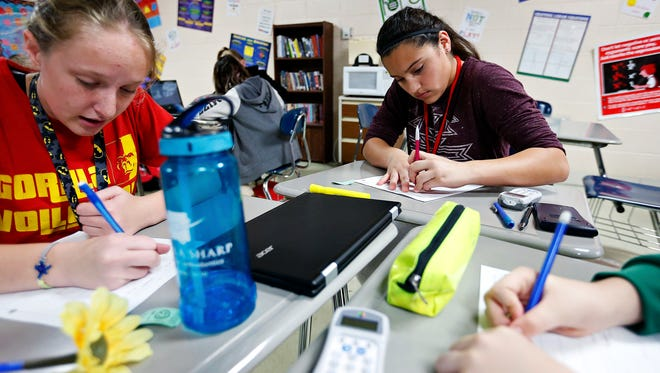 Madeline Nickles, left, 13, and Kasey Alvarez, 13, work on worksheets at their desks during a seventh-grade math class taught by Tiffany Jones at Nixa Junior High School in Nixa, Mo. on Nov. 16, 2016.