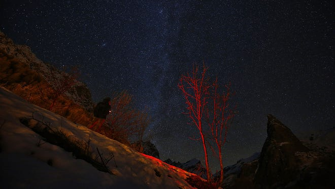 A photographer looks at the sky at night to see the annual Geminid meteor shower near Provenzales' rock, in Maira Valley, northern Italy, on Dec. 6, 2016. A new study says the entire universe could be a hologram.