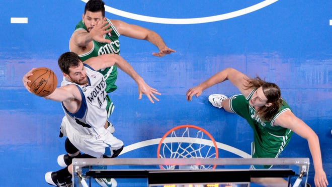 Minnesota Timberwolves forward Kevin Love (42) dunks while Boston Celtics center Vitor Faverani (38) and teammate forward Kelly Olynyk (41) defend during the third quarter at the Bell Centre.