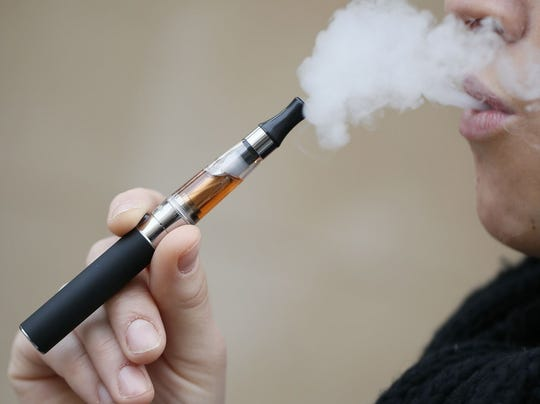 A person smoking an electronic cigarette in Paris.