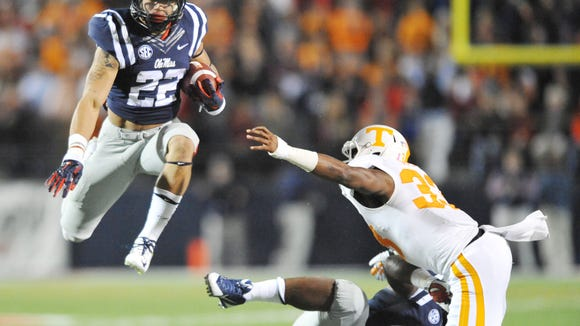 Mississippi  running back Jordan Wilkins (22) hurdles past Tennessee  defensive back LaDarrell McNeil (33) during the first half of an NCAA college football game at Vaught-Hemingway Stadium in Oxford, Miss. on Saturday, Oct. 18, 2014. (AP Photo/Oxford Eagle, Bruce Newman) MAGS OUT; NO SALES; MANDATORY CREDIT