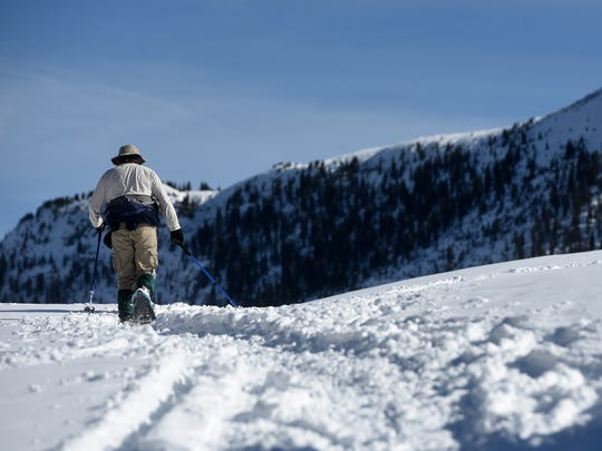 A snowshoer forges up one of the trails at Andrews Lake near Molas Pass on Friday.