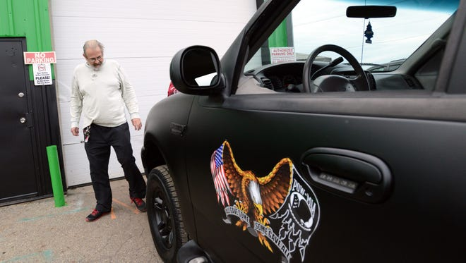 Navy veteran Bob Comyack, from Lancaster, walks around a Ford Expedition given to him by Allman Complete Auto & Truck Center and other local automotive businesses Nov. 17 in Lancaster. Comyack was given the sport utility vehicle after coming in to the shop for a free oil change on Veterans Day for his 1995 Jeep Cherokee.