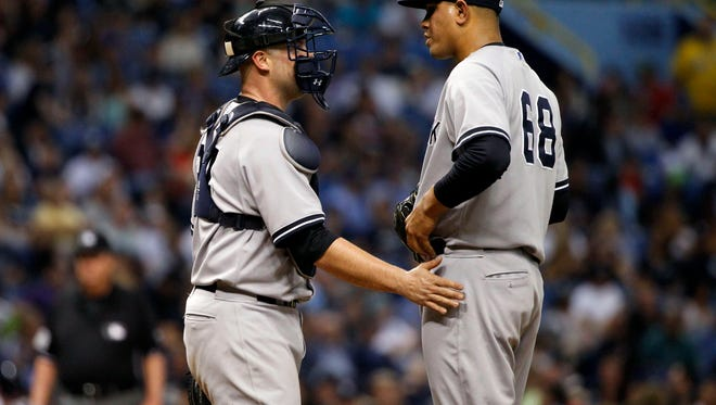 Yankees catcher Brian McCann, left, comes out to talk with relief pitcher Dellin Betances during the sixth inning against the Tampa Bay Rays at Tropicana Field.