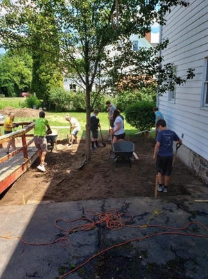 The mission team from Newark First United Methodist Church creates a patio for Family Promise of Wayne County.