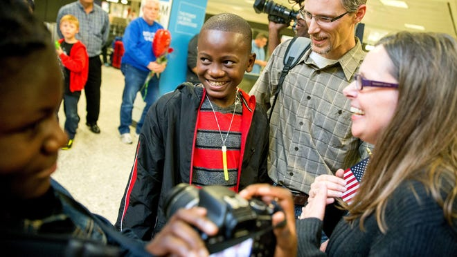 Jennifer and Eric Sands of Illinois, accompanied by daughter Joy, 12, greet their adopted son, Issaac, 12, as he arrives from Congo at Dulles International Airport in Virginia last year.