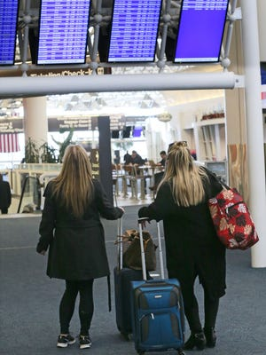 People study the arrival and departure boards at Milwaukee's Mitchell International Airport to see if flights are delayed or canceled due to weather.
