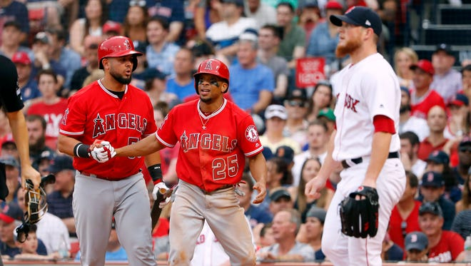 Los Angeles Angels left fielder Ben Revere (25) is congratulated by a teammate after scoring a run as Boston Red Sox relief pitcher Craig Kimbrel (46) walks back to the mound during the ninth inning of their 4-2 win at Fenway Park.