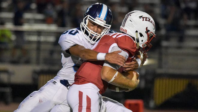 Texan's Qauterback Brad Breckenridge is sacked by the Tiger's Jonathan Tovar on Sept. 8, 2017 at Buccaneer Stadium.