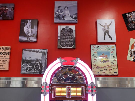 Vintage prints and a Crosley jukebox greet guests entering