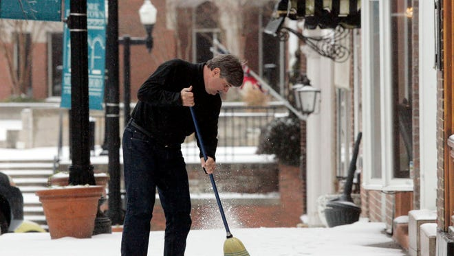 Attorney Rick Mansfield sweeps snow in front of his law office on the square Thursday in Murfreesboro.