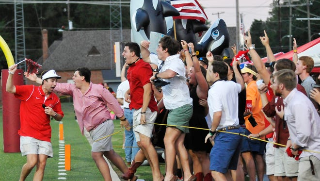 Huntingdon College fans react to a long touchdown run during their game with Birmingham Southern on Charles Lee Field at Huntingdon on Saturday, Sept. 11, 2014, in Montgomery, Ala.
