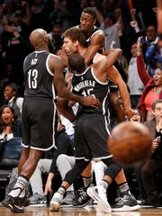 Teammates celebrate with Brooklyn Nets center Brook Lopez, center, after Lopez hit a shot in the waning seconds of the Nets 98-96 victory over the Detroit Pistons Tuesday, March 21, 2017, in New York.