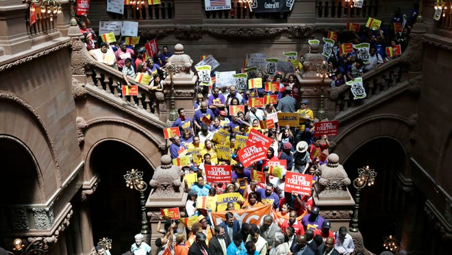 People rally for an increase in the minimum wage June 17 on the Great Western Staircase at the Capitol in Albany. New York's minimum wage will increase from $8 to $8.75 an hour on New Year's Eve.