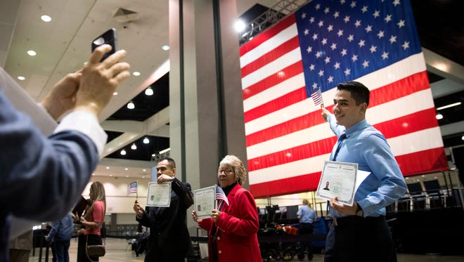 In this Feb. 15 photo, Erik Danialian, a 21-year-old immigrant from Iran, poses with his U.S citizenship certificate in front of a large U.S. flag after a naturalization ceremony at the Los Angeles Convention Center.