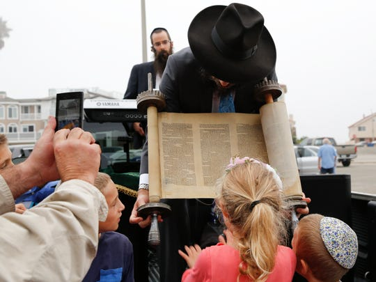Rabbi Dov Muchnik unveils a World War II-era Torah during a dedication ceremony last month. The Torah was rescued from Eastern Europe during World War II and donated to Chabad of Oxnard in commemoration of the chabad's 13th birthday.