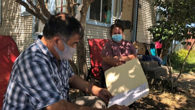 Irma Barbosa, an unemployed packing plant worker in Lodi, watches as farmworker advocate Luis Magana looks over eviction papers she received in July.