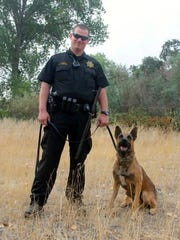 Officer Tyler Finch and K-9 Chance of the Anderson Police Department pose in this file photo. Chance chased down a driver from a stolen vehicle who shot the police dog in the left ear early Saturday morning, police said.