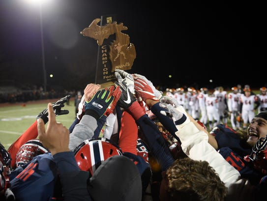 The Patriots hoist the Division 2-Region 2 championship trophy after a 31-29 win over Flushing.
