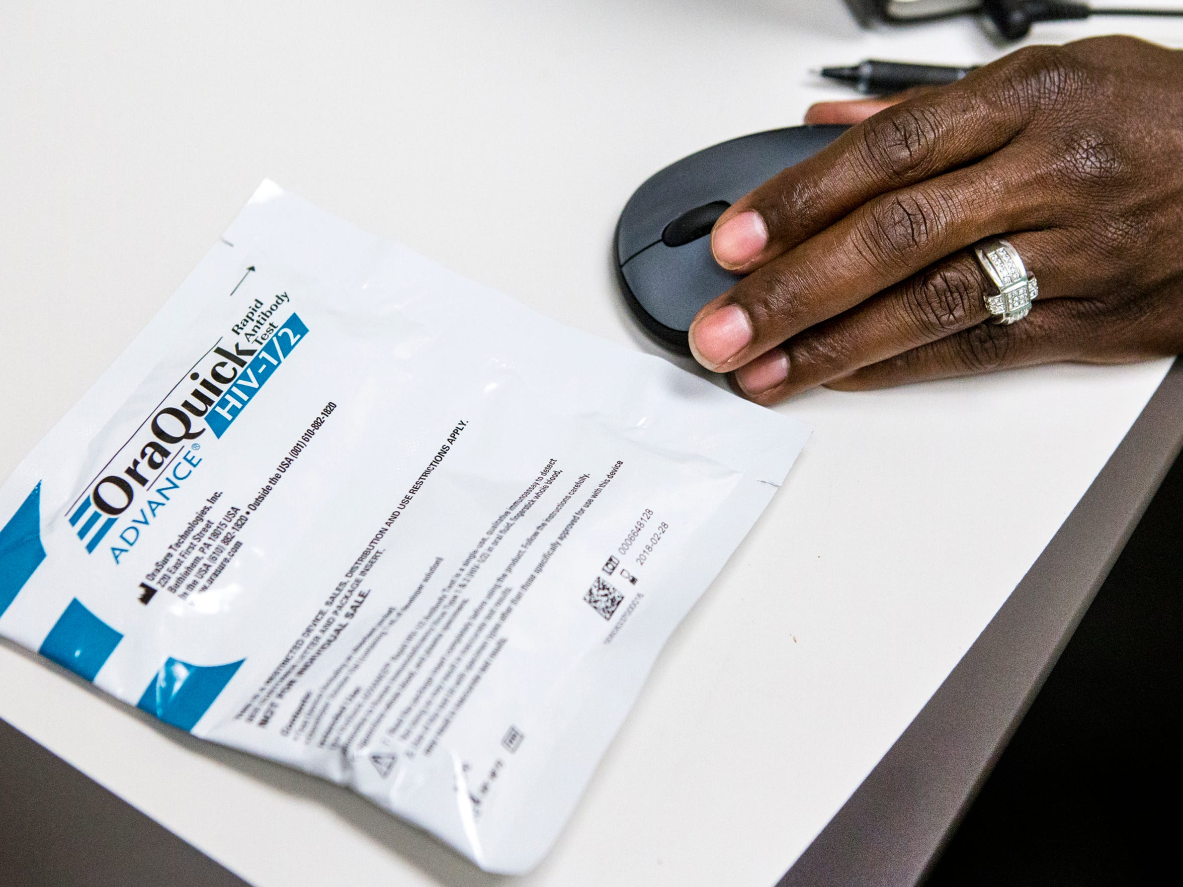 A sealed HIV test rests on a table next to Delaware HIV Consortium case manager Kenya Smoke at the Walgreens near Elsmere on Tuesday afternoon.