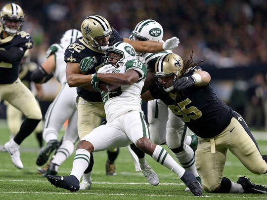 New York Jets running back Bilal Powell (29) is tackled by New Orleans Saints linebacker Craig Robertson (52) and defensive tackle Tyeler Davison (95) in the first quarter of the game at the Mercedes-Benz Superdome.