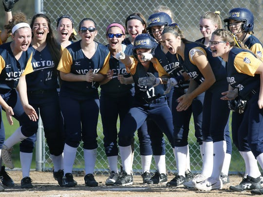 Victor teammates welcome Erin Wong at home plate during