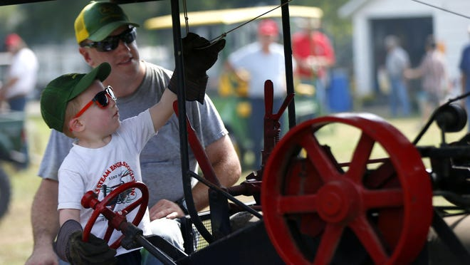 Ethan Brummett pulls a cable to blow the whistle on a steam engine as he drives it with his dad, Travis Brummett, at Steam-O-Rama last year.