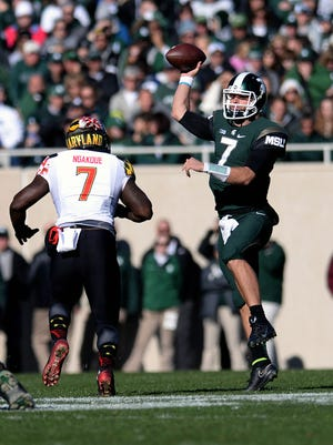 MSU quarterback Tyler O'Connor (7) makes a pass under pressure during the first half of the game against Maryland on Saturday at Spartan Stadium in East Lansing.