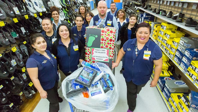 Wal-Mart employees walk a cart full of socks and other clothing items out of the store on Wednesday, December 21, 2016. About 75 employees at the supercenter on Walton Boulevard pitched in about 378 pairs of socks to be donated to the Gospel Rescue Mission.