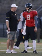 Iowa offensive coordinator Brian Ferentz, here talking with junior quarterback Tyler Wiegers on April 7 at Valley Stadium, says the QB race between Wiegers and Nathan Stanley is still too close to call.