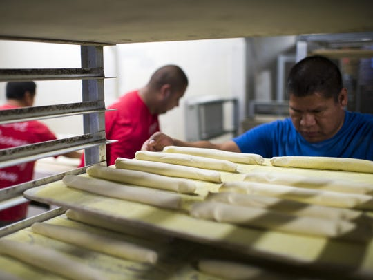Rocky Ventura, right, loads in trays of dough rolls