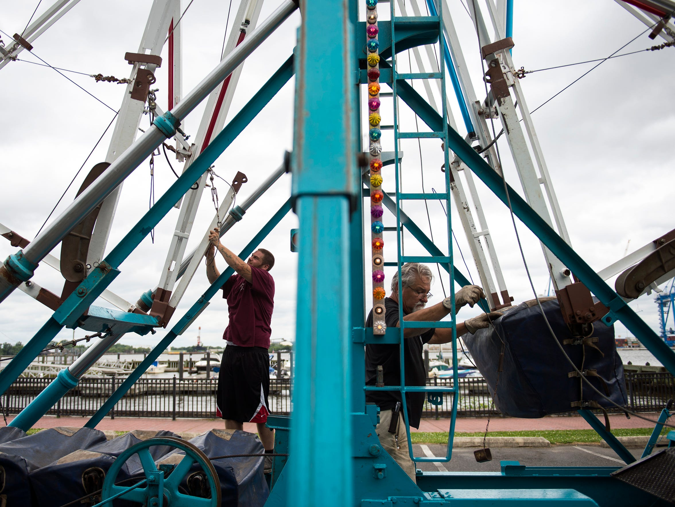 David Lynam, left, and Earl Derrickson of Lynam's Amusements set up a Ferris wheel Friday at Proprietors Park in Gloucester City. 'Not Your Mother's Music Fest' will be held Saturday, June 23.