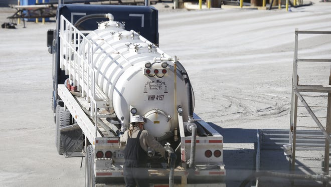 A truck driver works a tanker truck at a fracking wast water storage facility outside of Reno, Texas.