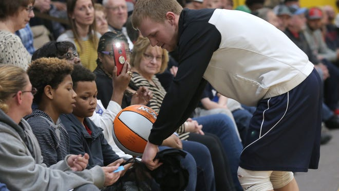 Lucas' Jackson Hauger gives a basketball to Mase Campbell, one of the All-Star kids, before the start of the 40th Annual News Journal All-Star Basketball Classic at Lexington High School. The event raised money for Catalyst Life Services.