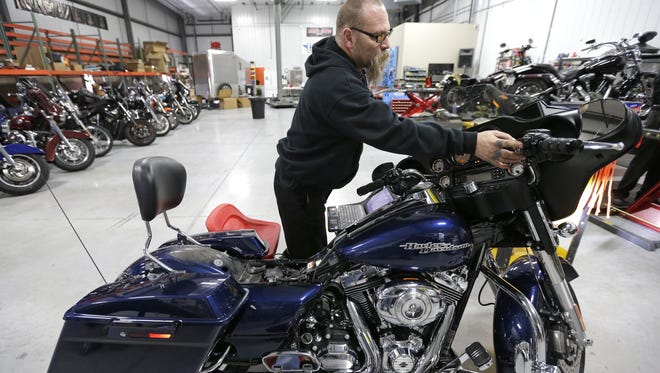 Mechanic Art Morales installs software for the air intake, exhaust and fuel systems of a 2012 Harley-Davidson Street Glide motorcycle at Mid-America Cycles' new facility in Appleton.